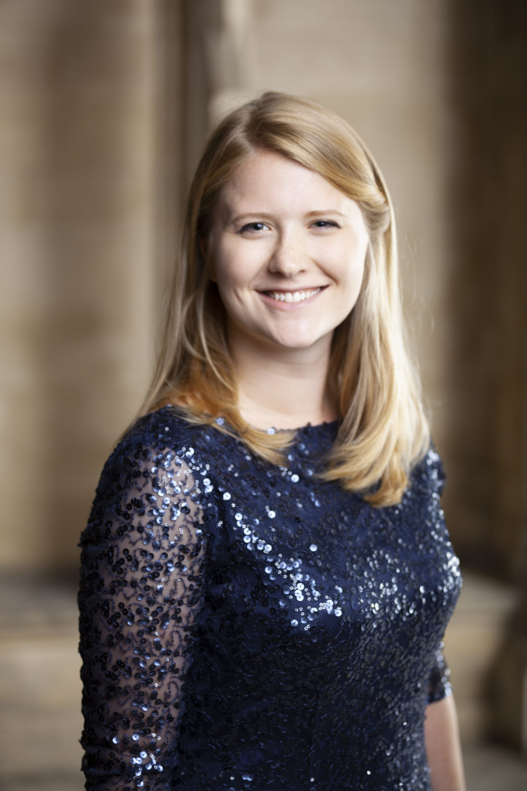 Sam Cobb, smiling at the camera, wearing a deep blue sparkly dress. Photo background: out of focus cloisters of New College.